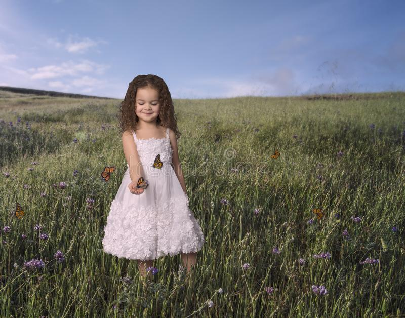 Kleines Mädchen im weißen Kleid, das Schmetterlinge hält stockfoto