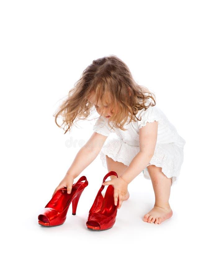Kleines Mädchen im weißen Kleid mit großen roten Schuhen lizenzfreies stockfoto