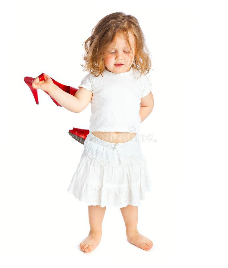 Kleines Mädchen im weißen Kleid mit großen roten Schuhen lizenzfreie stockfotos