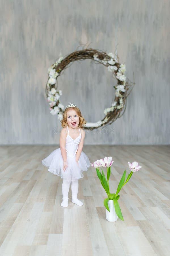 Kleines Mädchen im weißen Kleid und in den Tulpen wirft in einem schönen Studio auf lizenzfreie stockfotografie