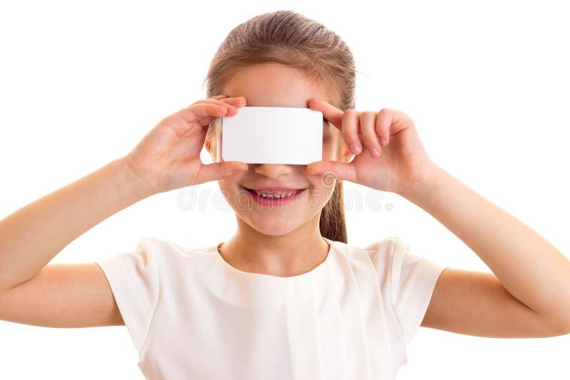 Kleines Mädchen im weißen T-Shirt, das weiße Karte hält stockbilder
