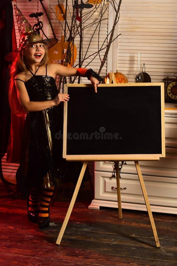Kleines Mädchen im Zaubererhutpunkt am Anzeigenbrett auf Halloween Kleines Mädchen in der Zaubererrobe mit Schulanzeige für stockbild