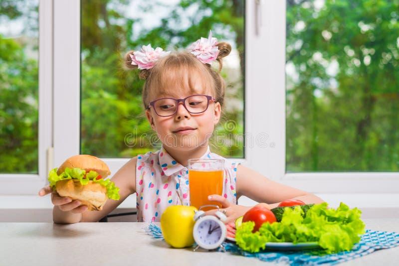 Kleines Mädchen isst am Fenster sitzend, gesunde Ernährung zu Abend lizenzfreie stockbilder