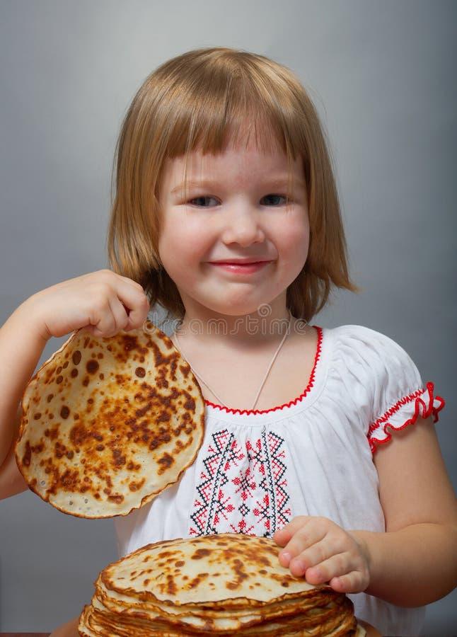 Kleines Mädchen isst Pfannkuchen lizenzfreie stockfotografie