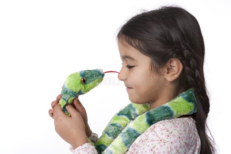 Kleines Mädchen ist hypnotizes durch eine Spielzeug-Schlange stockfoto
