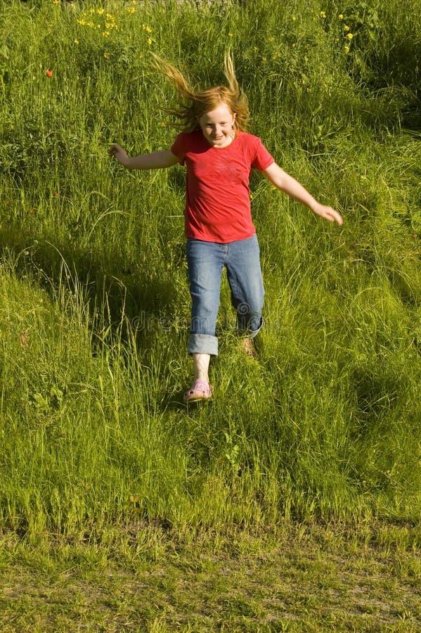 Kleines Mädchen ist Laufen eines Hügels stockfotografie