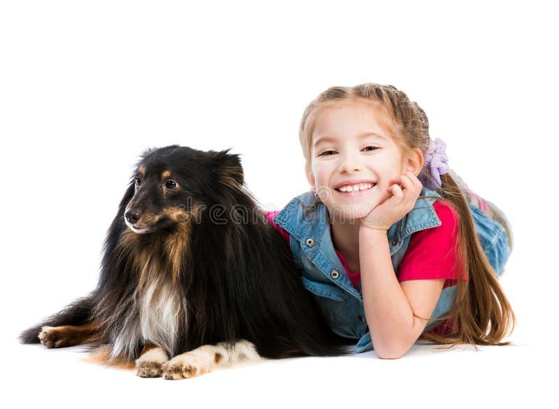 Kleines Mädchen ist mit ihrem Hund Sheltie lizenzfreies stockfoto