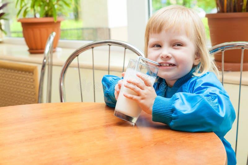 Kleines Mädchen ist Trinkmilch lizenzfreie stockbilder