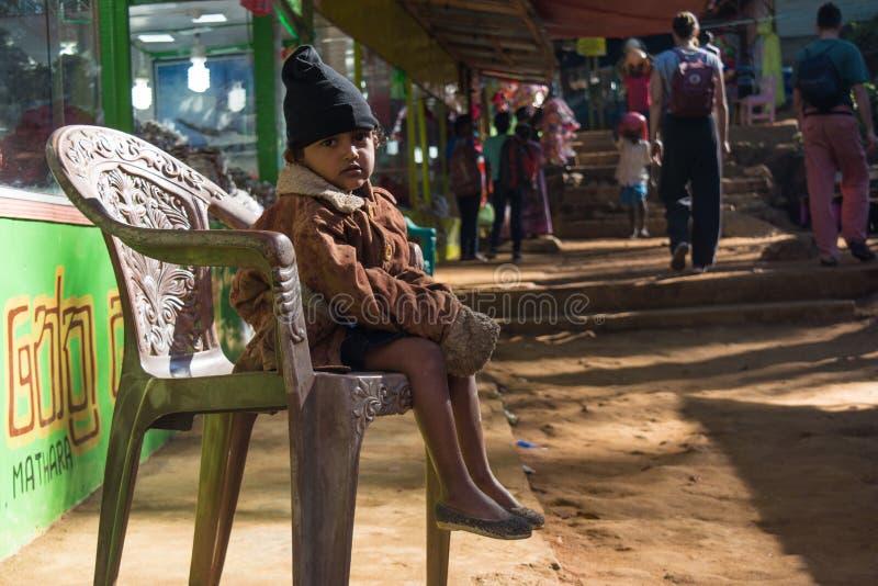 Kleines Mädchen kleidete in der warmen Kleidung an, die auf dem Stuhl in der Straße sitzt stockbilder
