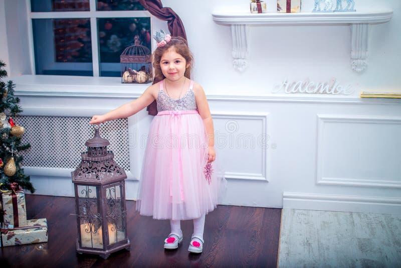Kleines Mädchen kleidete im schönen Kleid der weißen Blume der Mode an, das nahe Weihnachtsbaum aufwirft lizenzfreie stockfotos