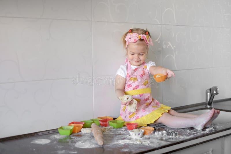 Kleines Mädchen kocht auf Küche Spaß bei der Herstellung von Kuchen und von Plätzchen haben lizenzfreie stockbilder