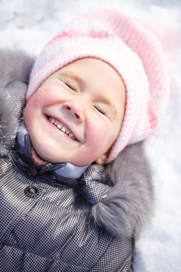 Kleines Mädchen legt auf einen Schnee lizenzfreies stockbild
