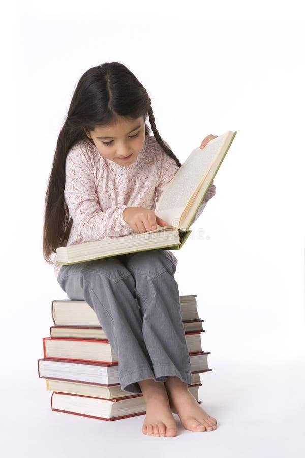 Kleines Mädchen liest ein großes Buch   stockfotografie