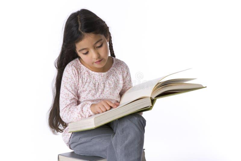 Kleines Mädchen liest ein großes Buch stockbilder