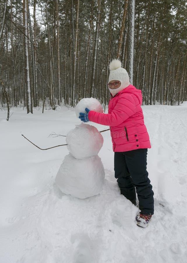 Kleines Mädchen macht einen Schneemann stockfoto