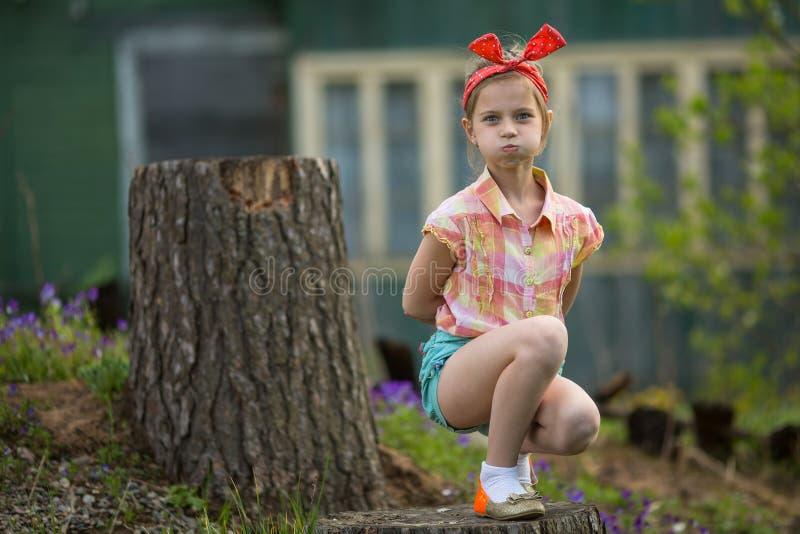 Kleines Mädchen macht Gesichter an der Kamera beim Sitzen nahe Landhaus lizenzfreie stockfotografie