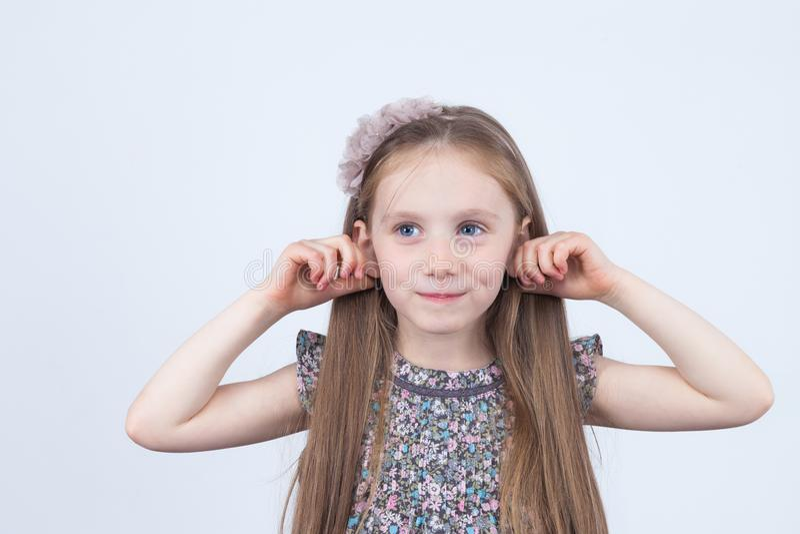 Kleines Mädchen macht Gesichter Lustige Ausdrücke Spaß haben Vorschüler im Kleid auf weißem Hintergrund lizenzfreies stockfoto