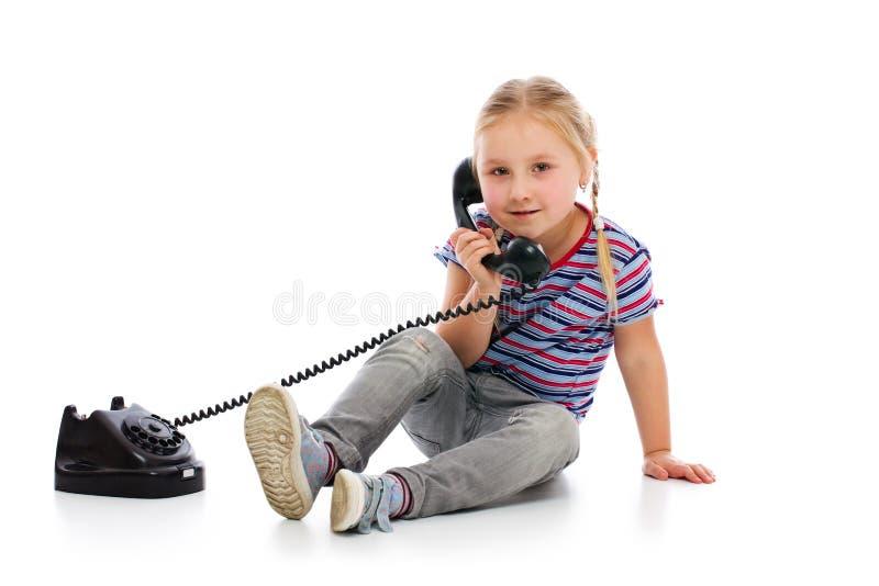Kleines Mädchen mit altem Retro- Telefon. stockfotos