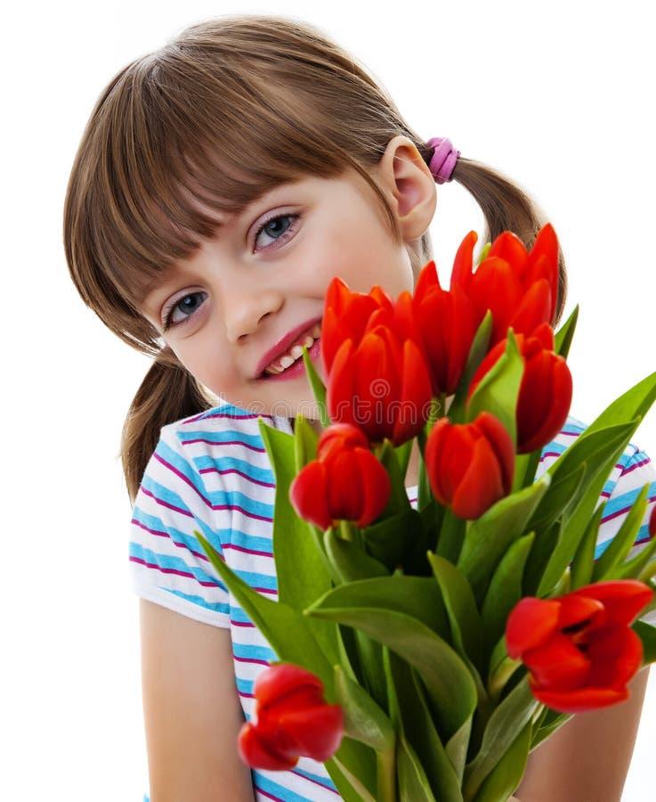 Kleines Mädchen mit Bündel roten Tulpen schließen oben lizenzfreies stockfoto