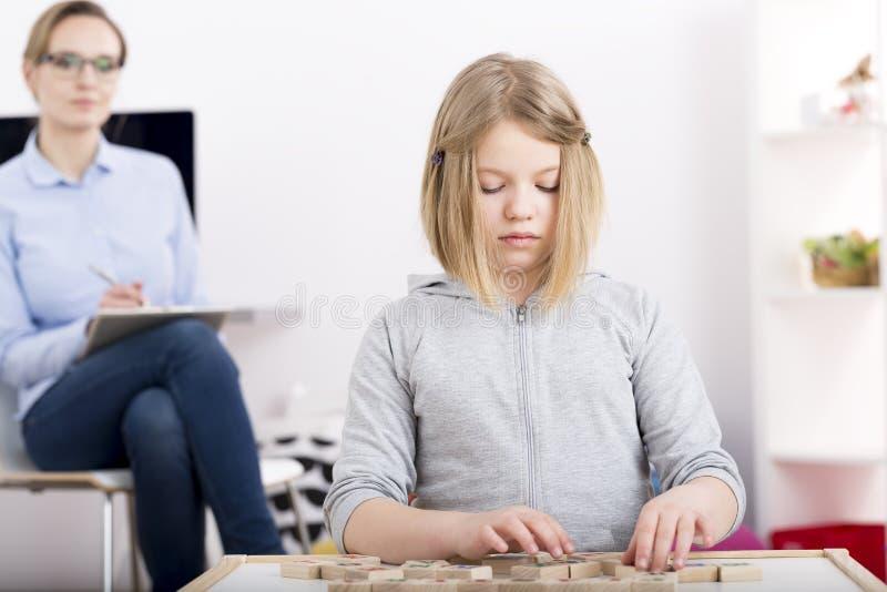 Kleines Mädchen mit Bausteinen mit Buchstaben stockfotos