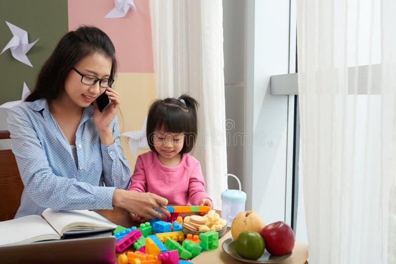 Kleines Mädchen mit berufstätiger Frau zu Hause lizenzfreies stockbild