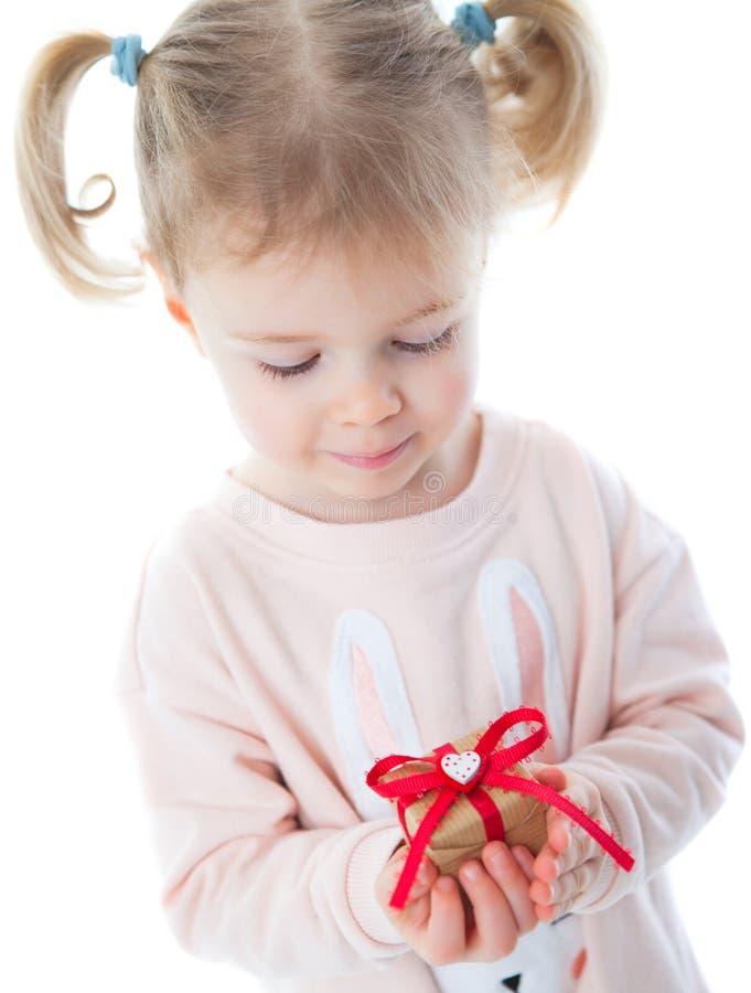 Kleines Mädchen mit Blumen und einem Geschenk lizenzfreie stockbilder