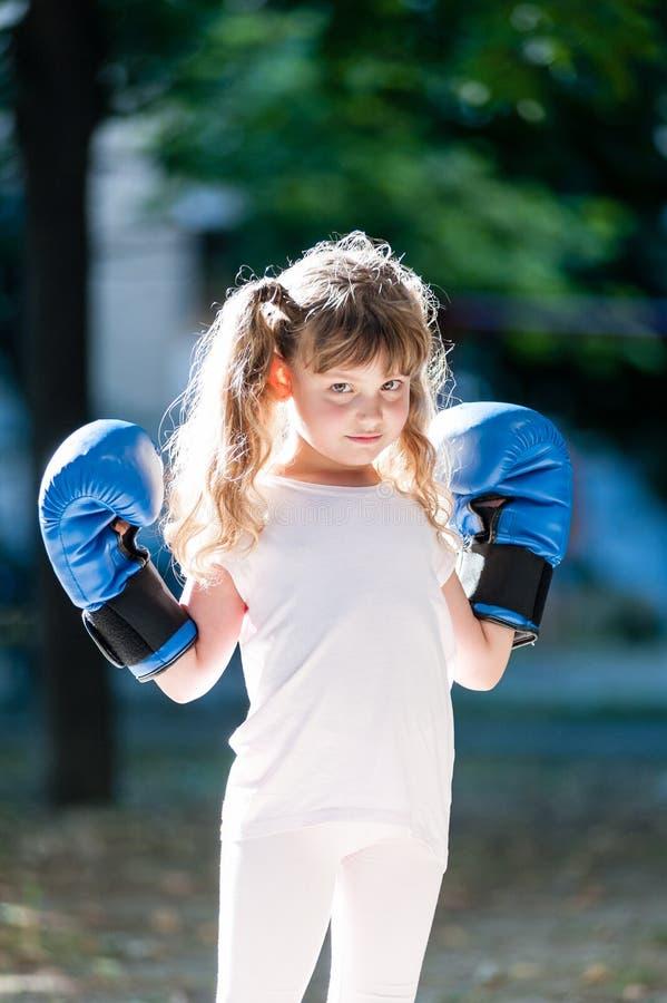 Kleines Mädchen mit Boxhandschuhen stockfoto