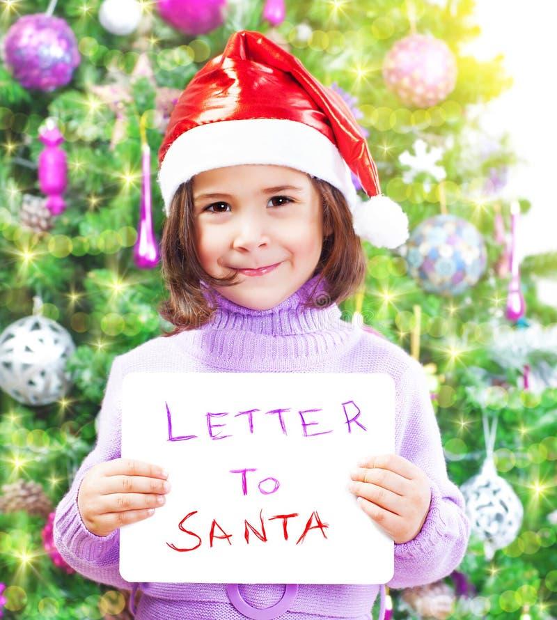 Kleines Mädchen mit Buchstaben zu Santa Claus stockfoto