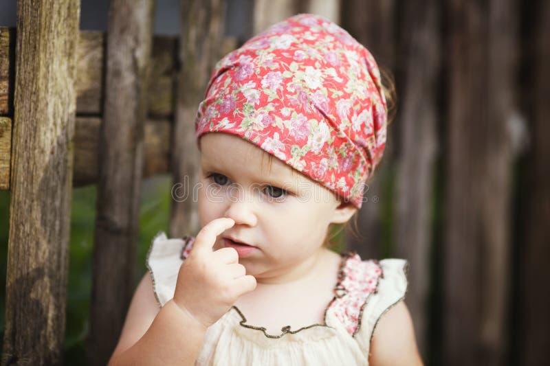 Kleines Mädchen mit dem Finger in ihrer Nase stockfotografie