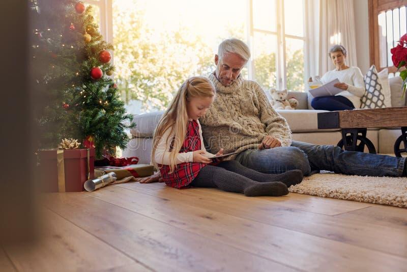 Kleines Mädchen mit dem Großvater, der zu Hause digitale Tablette während verwendet lizenzfreie stockfotos
