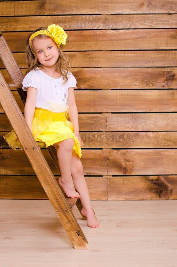 Kleines Mädchen mit dem Kranz, der auf Treppe der Leiter sitzt lizenzfreie stockfotografie