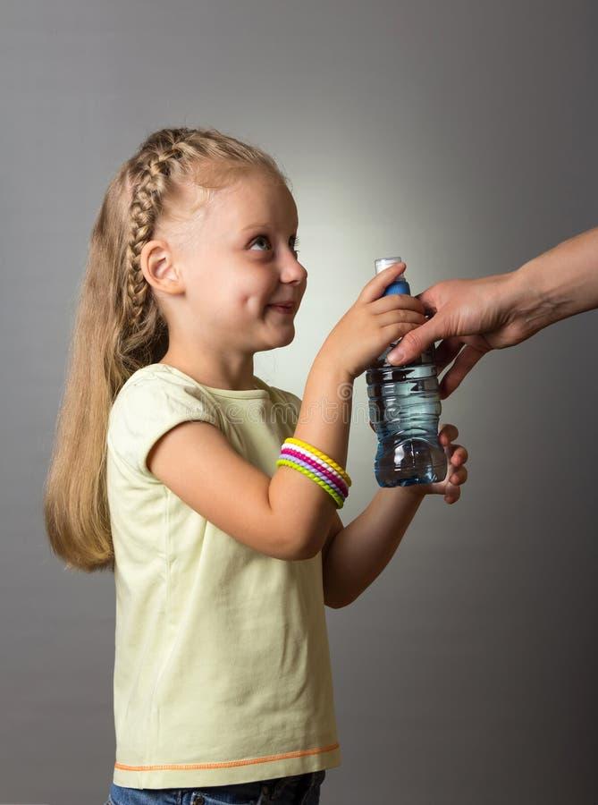 Kleines Mädchen mit dem schönen Haar nimmt von einem Erwachsenen eine Flasche Wasser stockfotos