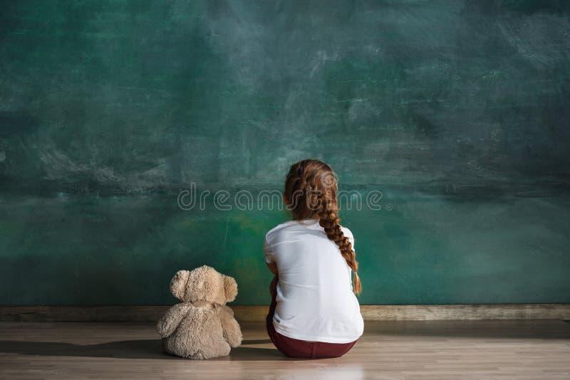 Kleines Mädchen mit dem Teddybären, der auf Boden im leeren Raum sitzt Autismus-Konzept stockfoto
