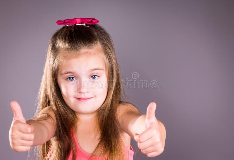Kleines Mädchen mit den blauen Augen, die sich Daumen zeigen lizenzfreie stockfotos
