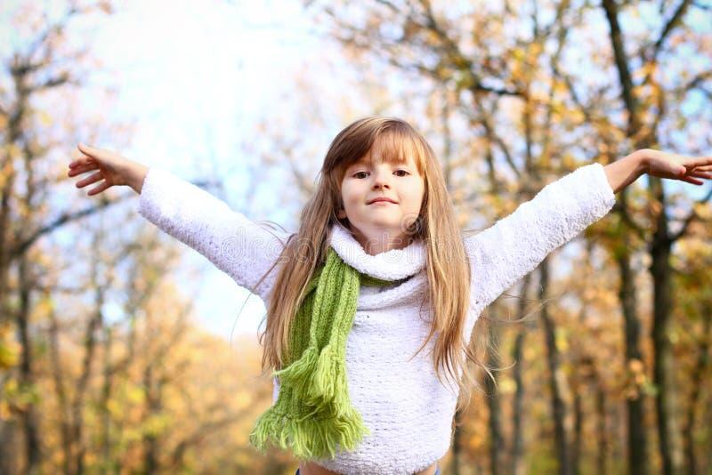 Kleines Mädchen mit den Händen oben im Herbstwald lizenzfreies stockbild