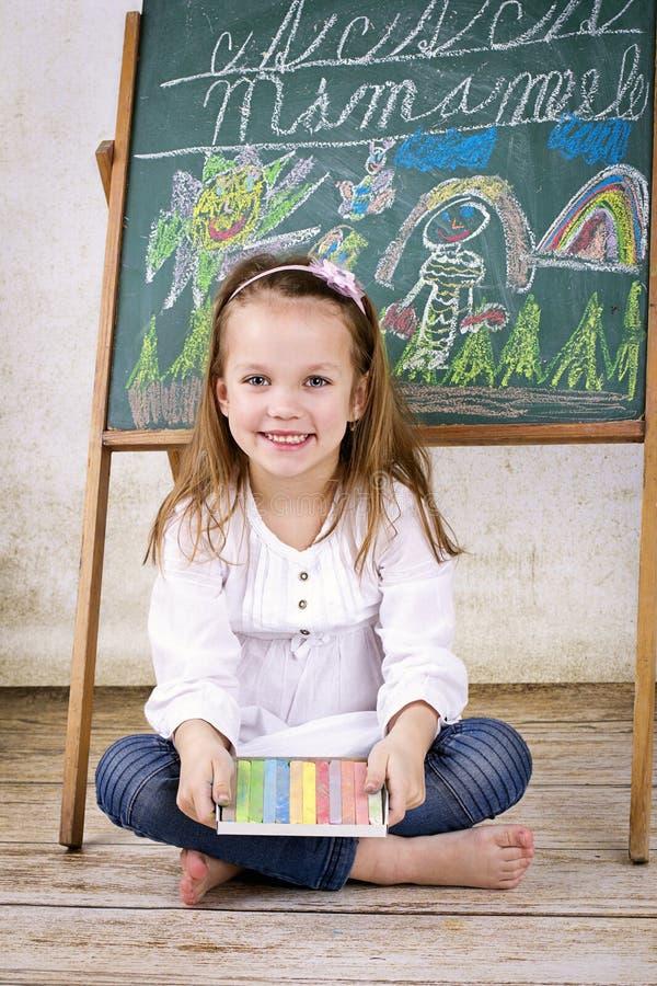 Kleines Mädchen mit den Kreiden, die vor der Tafel sitzen stockfotografie