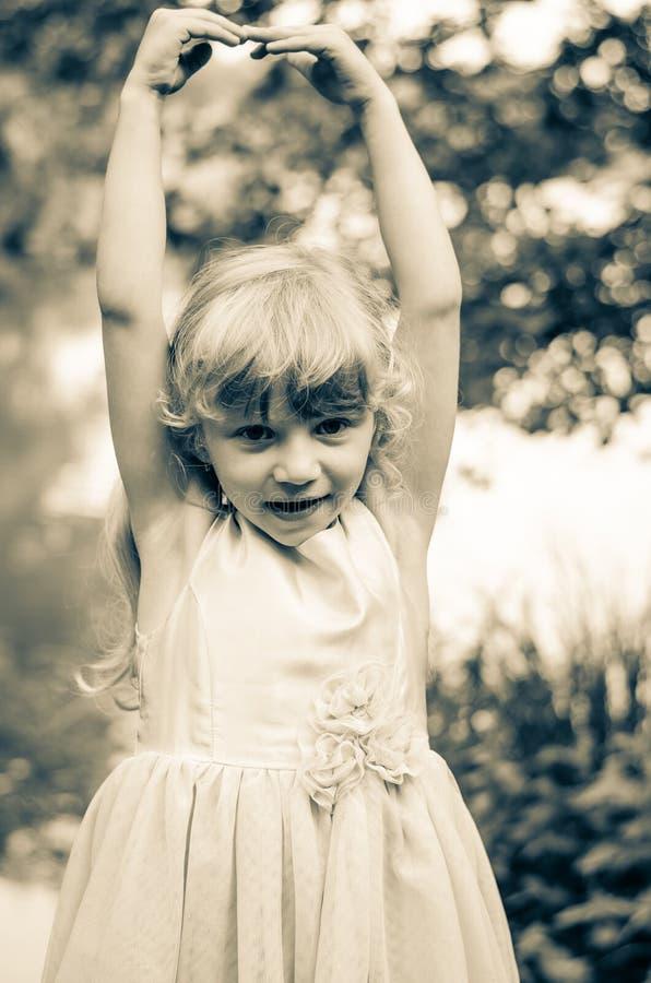 Kleines Mädchen mit den rised Händen stockfotos