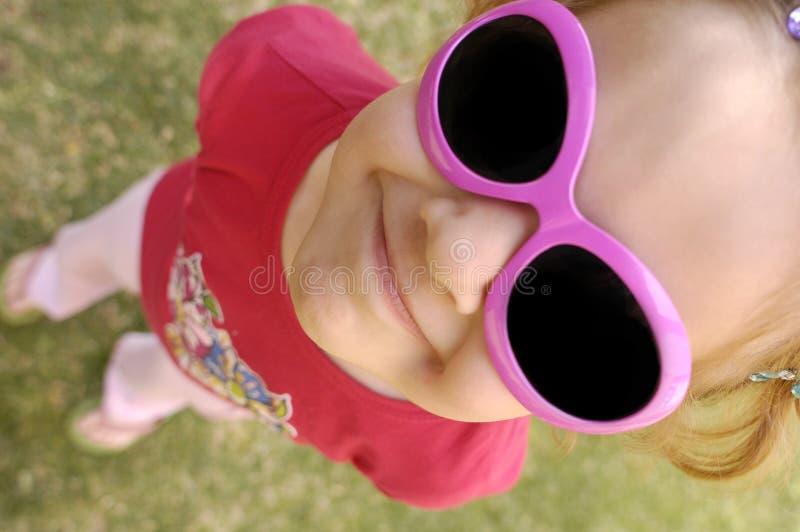 Kleines Mädchen mit den rosafarbenen Sonnenbrillen, die oben schauen stockfotografie