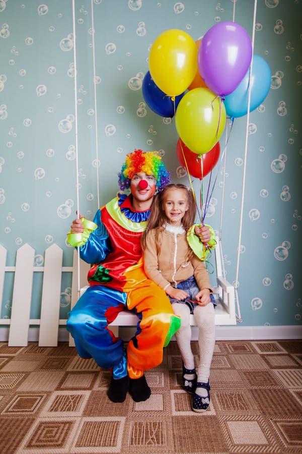 Kleines Mädchen mit der Clownerschütterung auf einem Schwingen stockbild