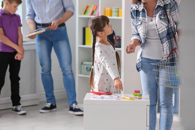 Kleines Mädchen mit der Mutter, die Schulbriefpapier wählt stockbild