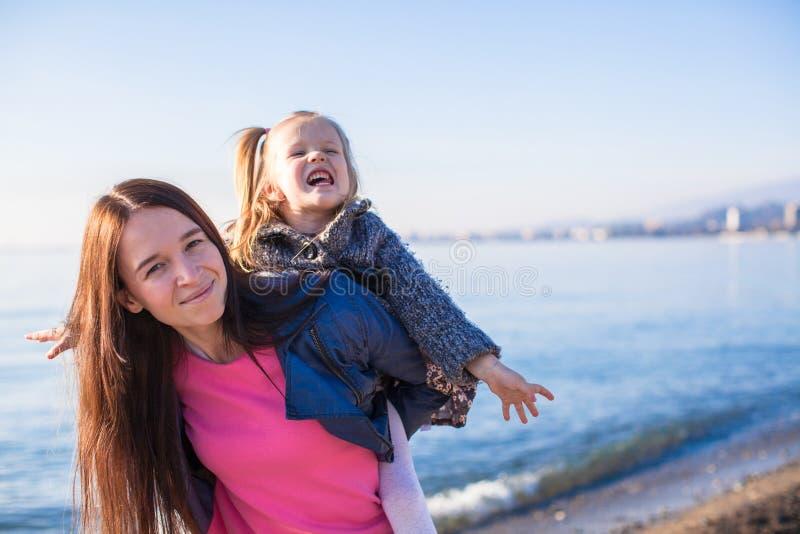 Kleines Mädchen mit der Mutter, die Spaß auf dem Strand in a hat lizenzfreie stockfotos