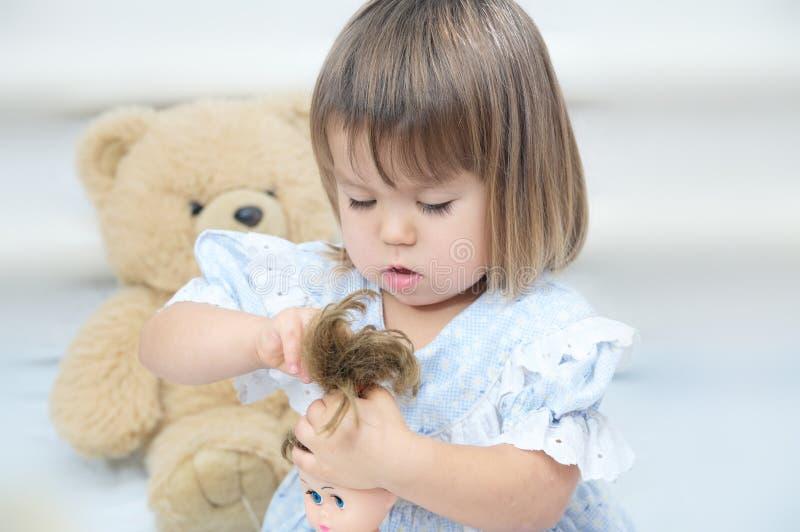 Kleines Mädchen mit der Puppe, die das Haarspielen kämmt stockfoto