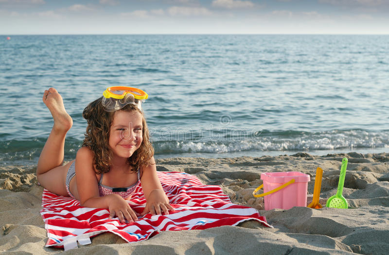 Kleines Mädchen mit der Tauchmaske, die auf Strand liegt stockbild