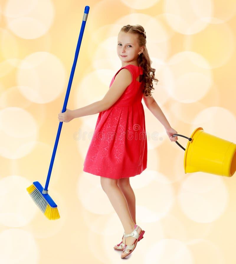 Kleines Mädchen mit Eimer und Bürste säubert das Haus stockbild