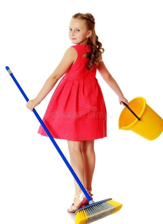 Kleines Mädchen mit Eimer und Bürste säubert das Haus stockfoto