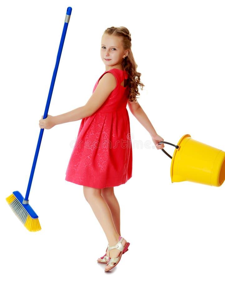 Kleines Mädchen mit Eimer und Bürste säubert das Haus lizenzfreies stockbild