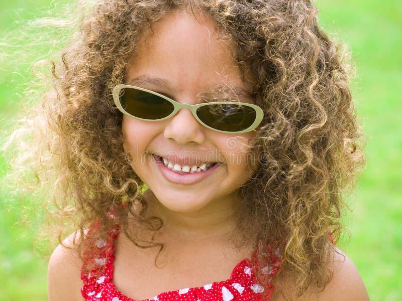 Kleines Mädchen mit ein helles Lächeln-tragenden Sonnenbrillen stockfoto
