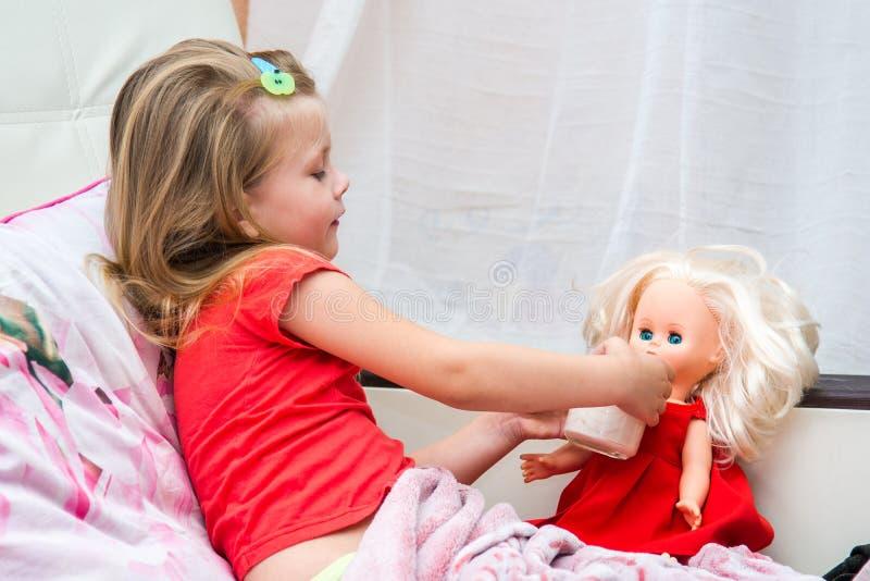 Kleines Mädchen mit einem Becher Milch stockbild