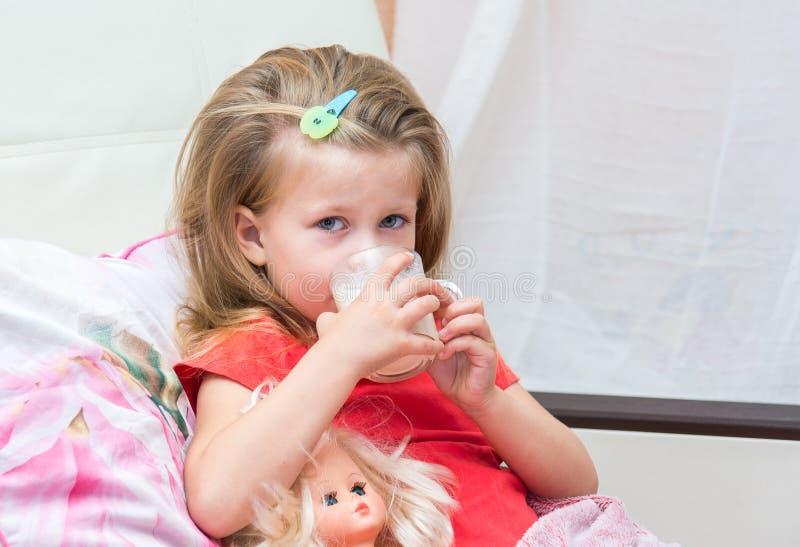 Kleines Mädchen mit einem Becher Milch lizenzfreies stockbild