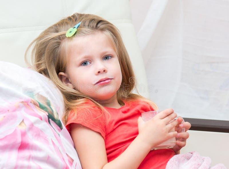 Kleines Mädchen mit einem Becher Milch lizenzfreie stockfotos